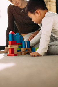Child playing colorful blocks game with mother