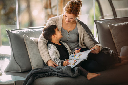 Mother and son with story book at home
