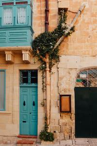 Blue wooden door in a wall of stone bricks