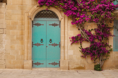Ancient maltese house with blue wooden door and pink bougainvillea in the wall