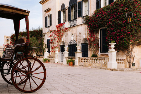 Ancient maltese house with orange bougainvillea in the wall and a buggy in the street