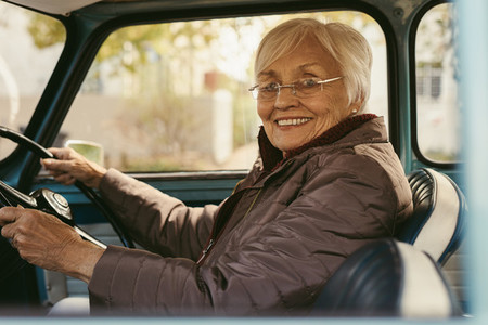 Senior woman driving a car on winter day