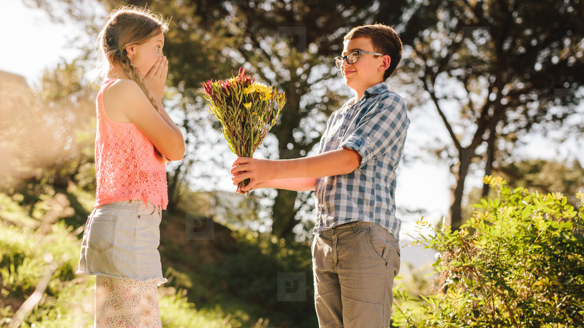 Boy giving a bouquet of flowers to his girlfriend in a park