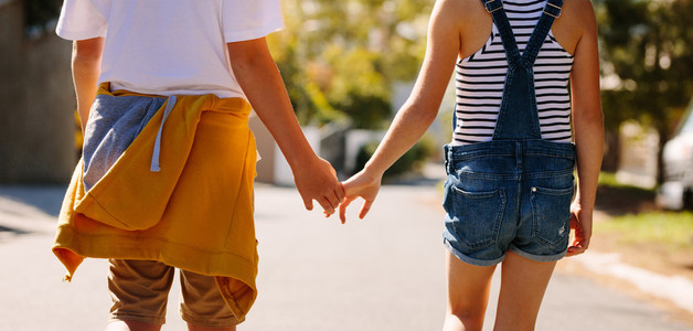 Kids in love walking on road holding hands