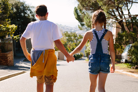 Rear view of kids walking on road holding hands
