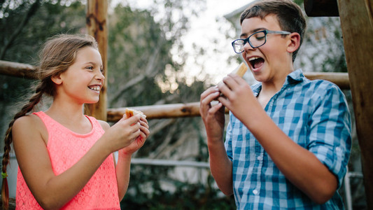 Kids eating picnic food standing outdoors