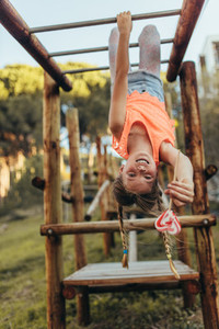 Girl hanging upside down on a horizontal ladder in a park