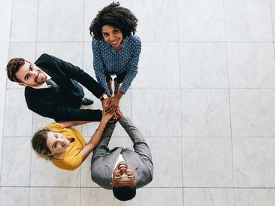Multi ethnic business team with hands stacked together