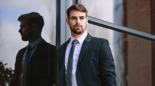 Businessman standing by office building outdoors