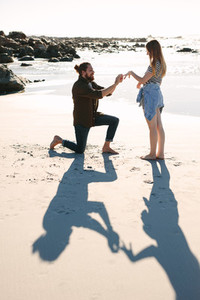 Man proposing marriage to his girlfriend on the beach