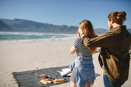 Boyfriend giving surprise to his girlfriend at the beach