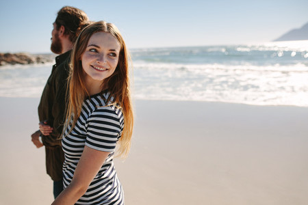 Woman walking on the beach with boyfriend