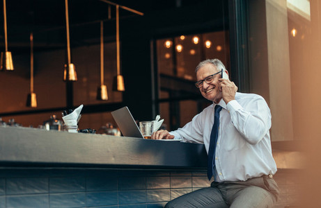 Senior businessman at cafe making a phone call