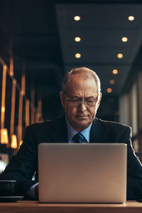 Senior businessman at cafe working on laptop
