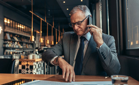 Senior businessman waiting for someone at cafe