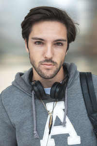 Portrait of confident handsome young man  with headphones in the stairs of campus
