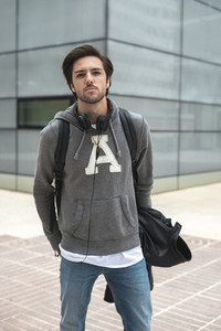 Portrait of handsome young man with a black backpack and headphones in the campus
