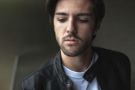 Close up portrait of handsome confident young man looking down w