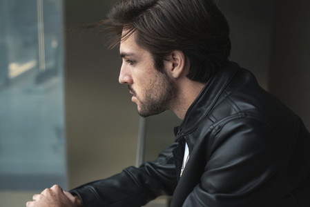 Portrait of handsome confident young man looking through the window wearing black leather jacket