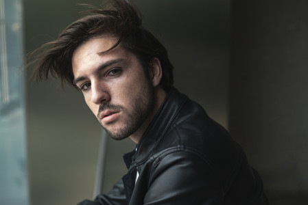 Portrait of handsome confident young man looking at camera with hair blowing by wind  wearing black leather jacket