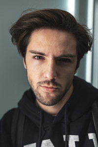 Close up portrait of handsome confident young man looking at camera wearing sweatshirt