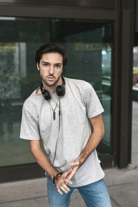 Portrait of confident handsome young man  with headphones in the campus