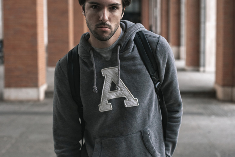 Portrait of confident young man in the campus with a black backpack