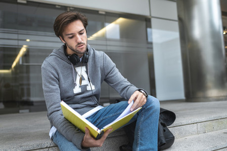 Young man reading a handwriting notebook seated in the stairs of campus