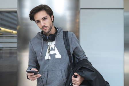 Young man chatting with mobile phone wearing headphones in the stairs of campus