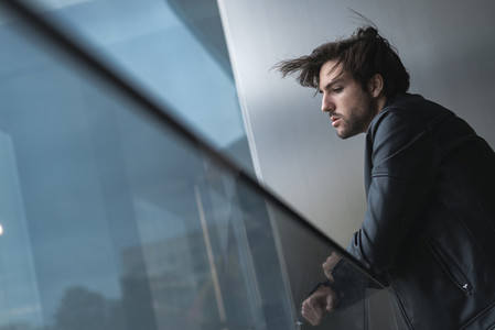 Low angle view of handsome confident young man looking through the window with hair blowing by the wind wearing a black leather jacket