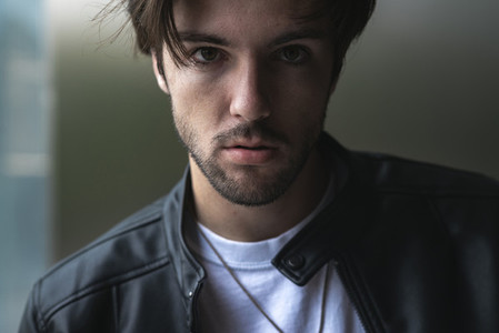 Close up portrait of handsome confident young man looking at camera wearing black leather jacket