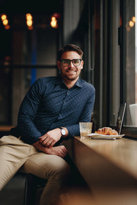 Smiling man sitting in restaurant with food and laptop on table
