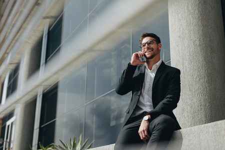 Smiling business person taking on mobile phone sitting outdoors