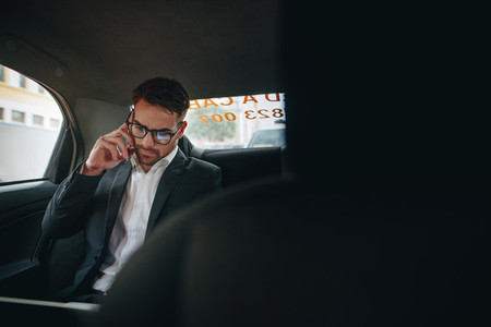 Businessman doing office work while travelling to office in a ca