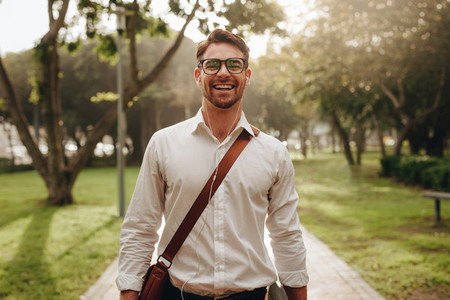 Cheerful businessman walking through a park going to office