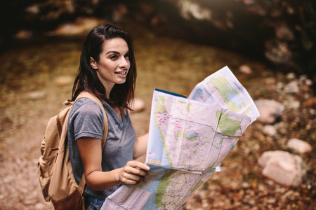 Beautiful woman hiker with a map