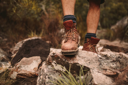 Man hiking through rocky path in trekking boots