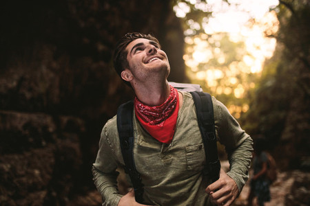 Smiling young guy hiking in mountain and looking up