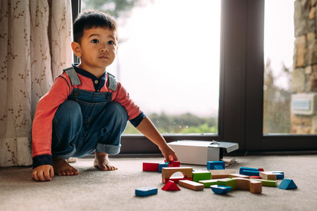 Innocent little kid with toys on floor