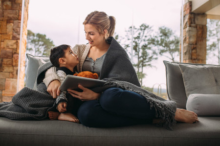 Woman talking with son sitting at home