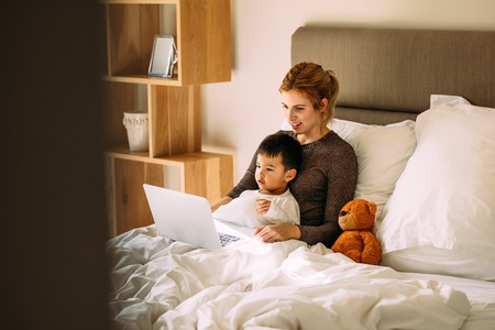 Mother and son watching cartoons on laptop in bed