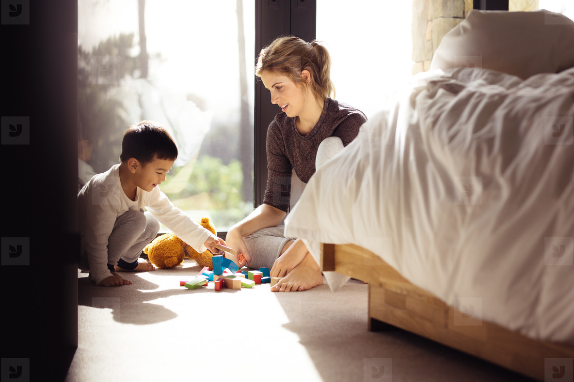 Woman looking at her son playing blocks indoors