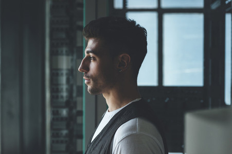 Portrait of a handsome man looking through the window in an abandoned building