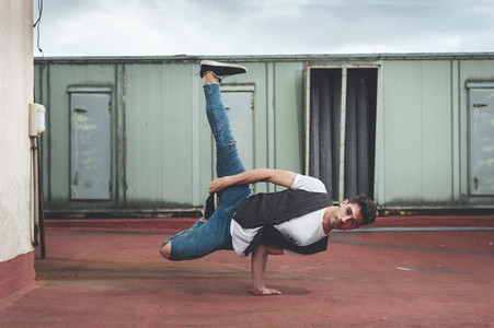 Stylish bboy performing a break dance stance close to green machinery in the rooftop of a building