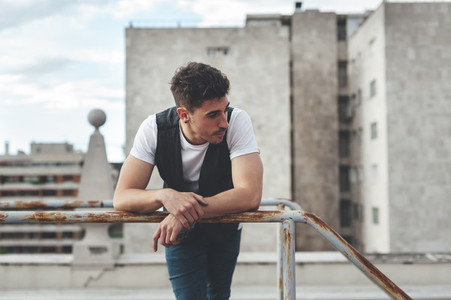 Portrait of a handsome man leaning on an iron handrail in the rooftop of a building