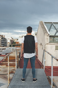 Back view of a handsome man standing in the rooftop of a building