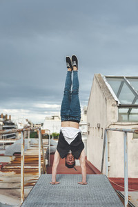 Stylish bboy performing a break dance stance in a metal staircase in the rooftop of a building