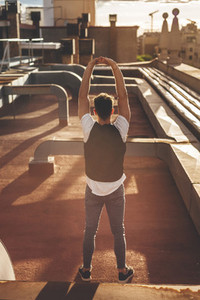 Back view of a handsome man stretching in the rooftop of a building at sunset