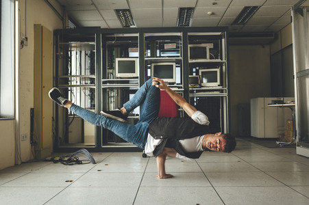 Stylish bboy performing a break dance stance in an abandoned building