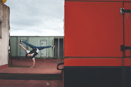 Stylish bboy performing a break dance stance close to red and green machinery in the rooftop of a building